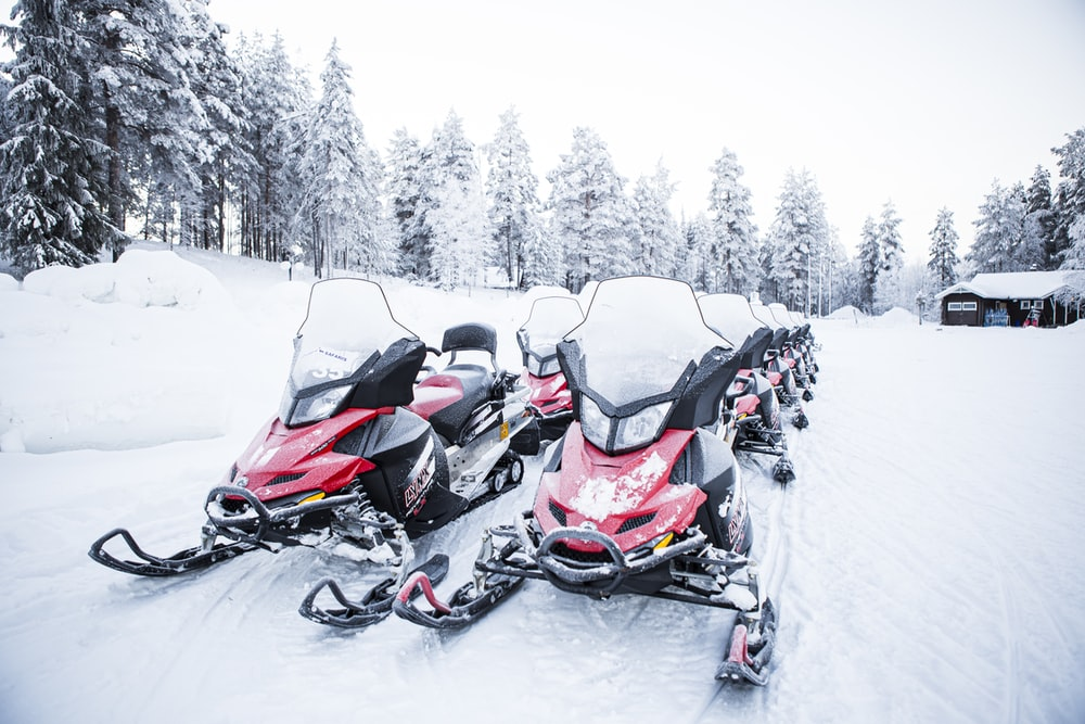black and orange snow mobile on snow covered ground