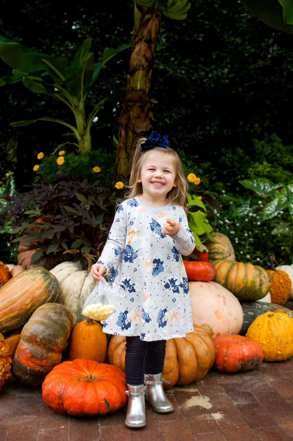 girl in white and blue floral dress standing on pumpkin field during daytime