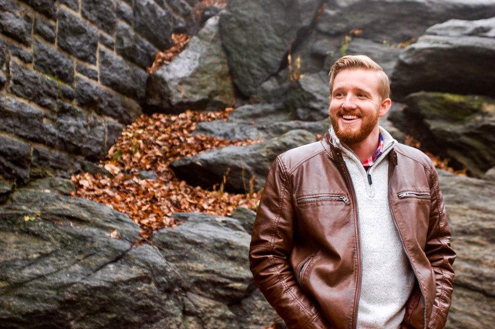man in brown leather jacket standing near gray rocks during daytime