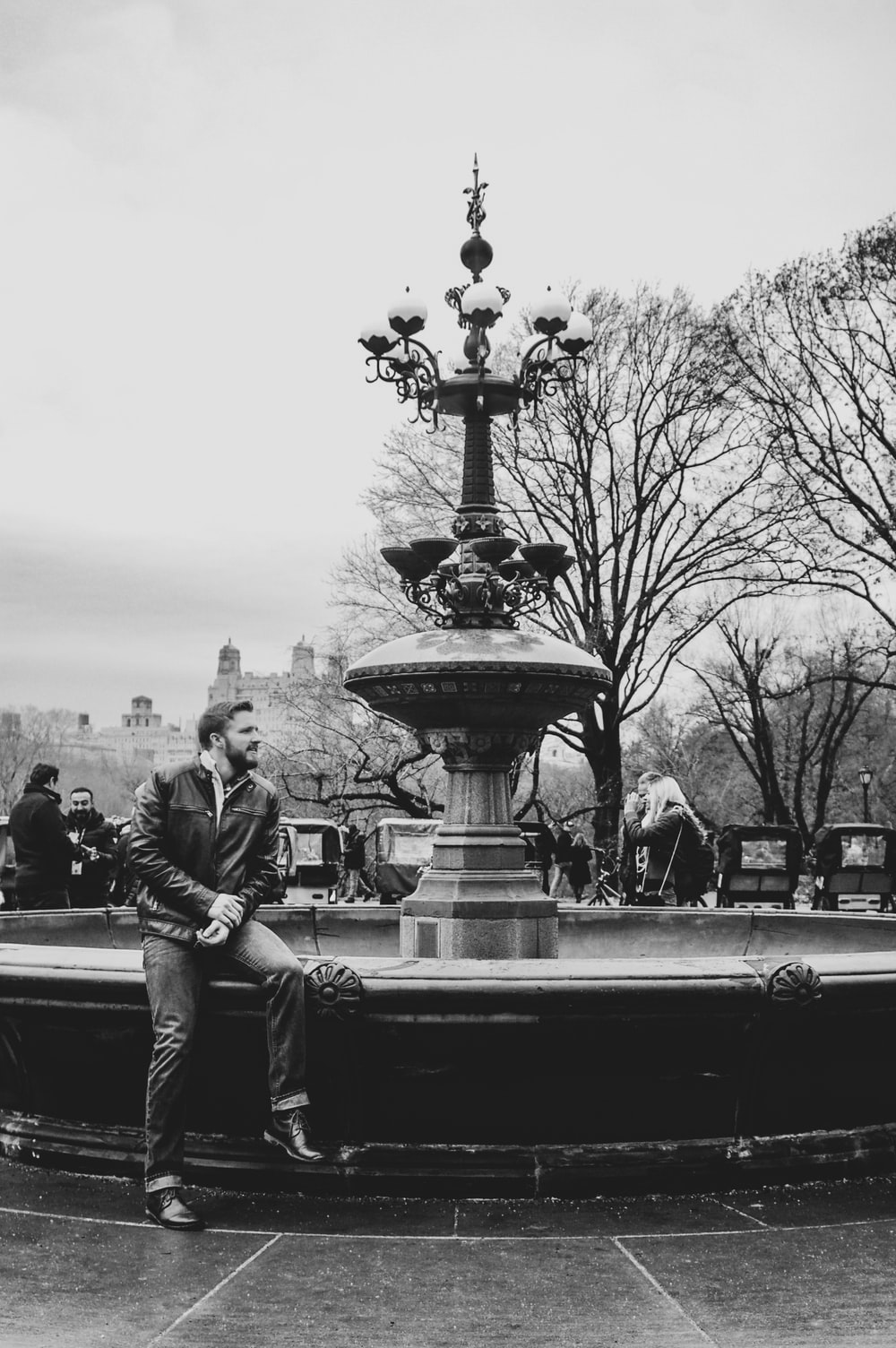 grayscale photo of 2 men sitting on round outdoor fountain