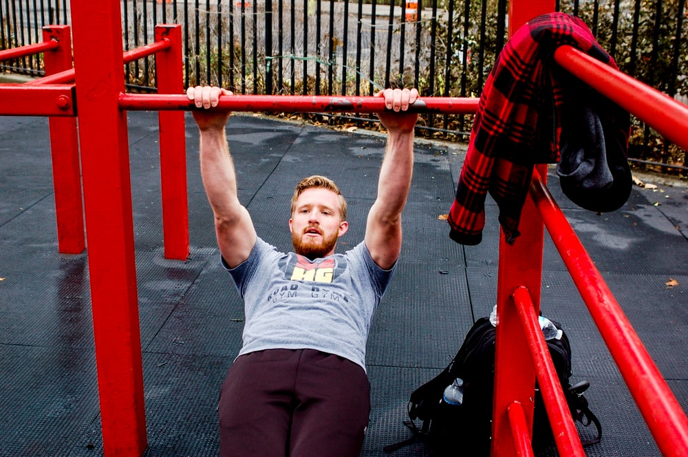 man in gray crew neck t-shirt and black shorts holding red metal bar
