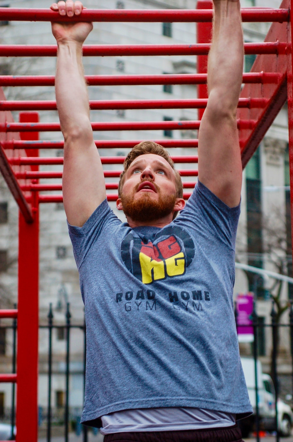 man in gray crew neck t-shirt standing and raising his hands