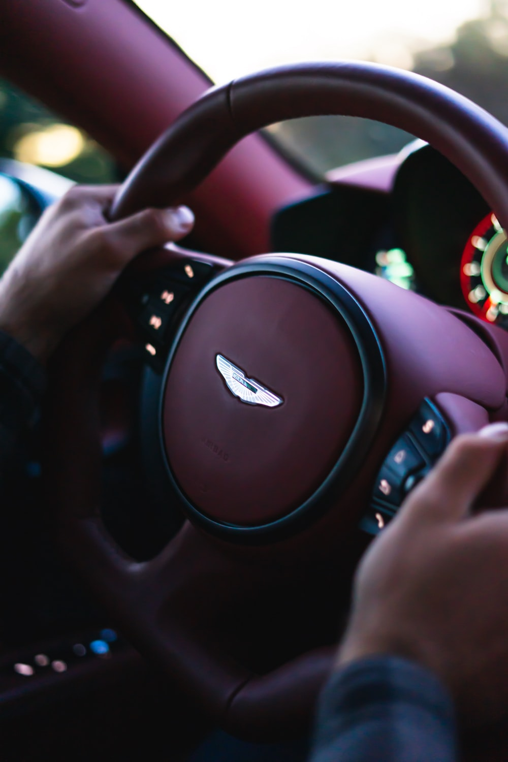 person holding black and silver steering wheel