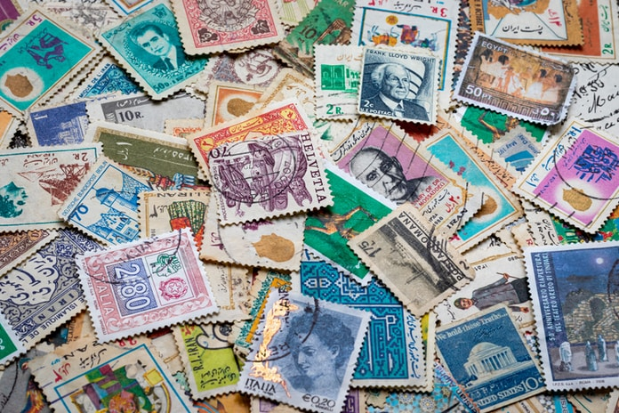 assorted postage stamps on blue and white textile
