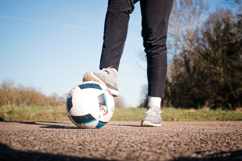 person in black pants and white nike soccer ball