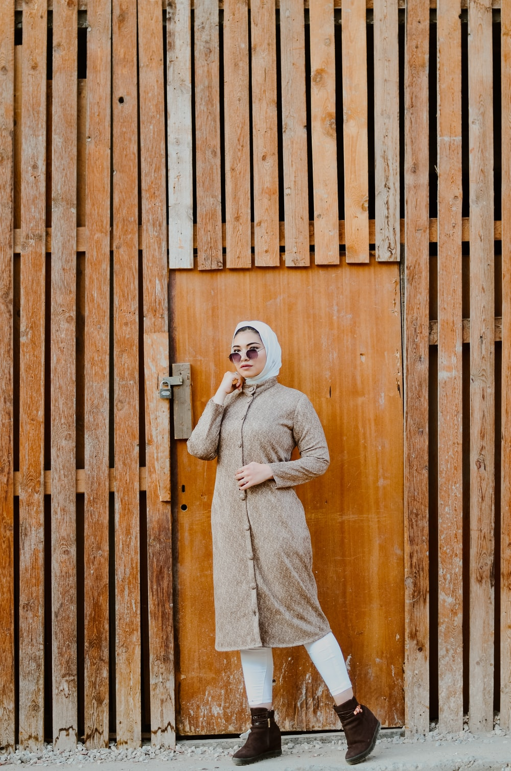 woman in brown long sleeve dress wearing white hijab standing beside brown wooden wall