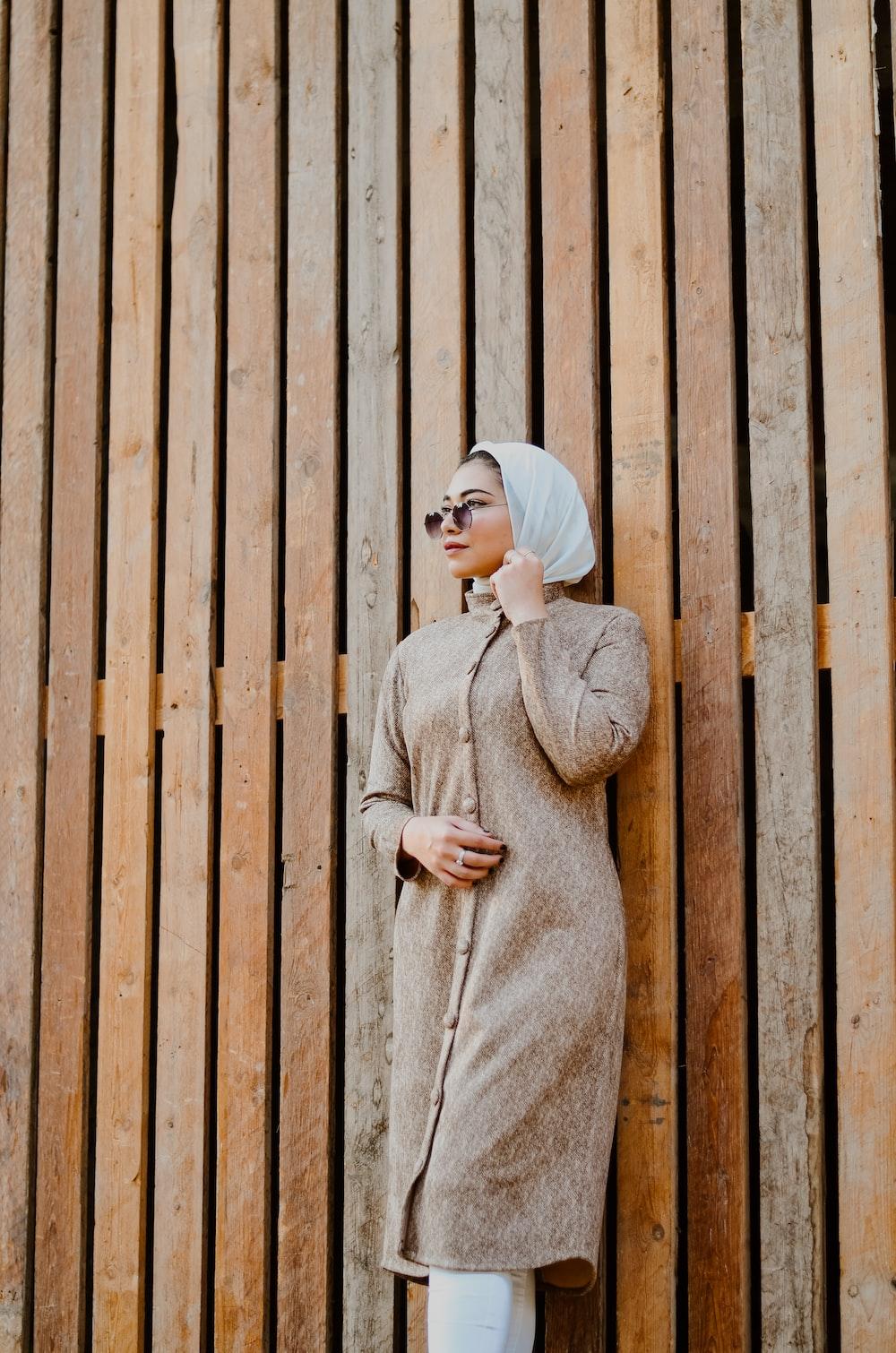woman in beige sweater standing beside brown wooden wall