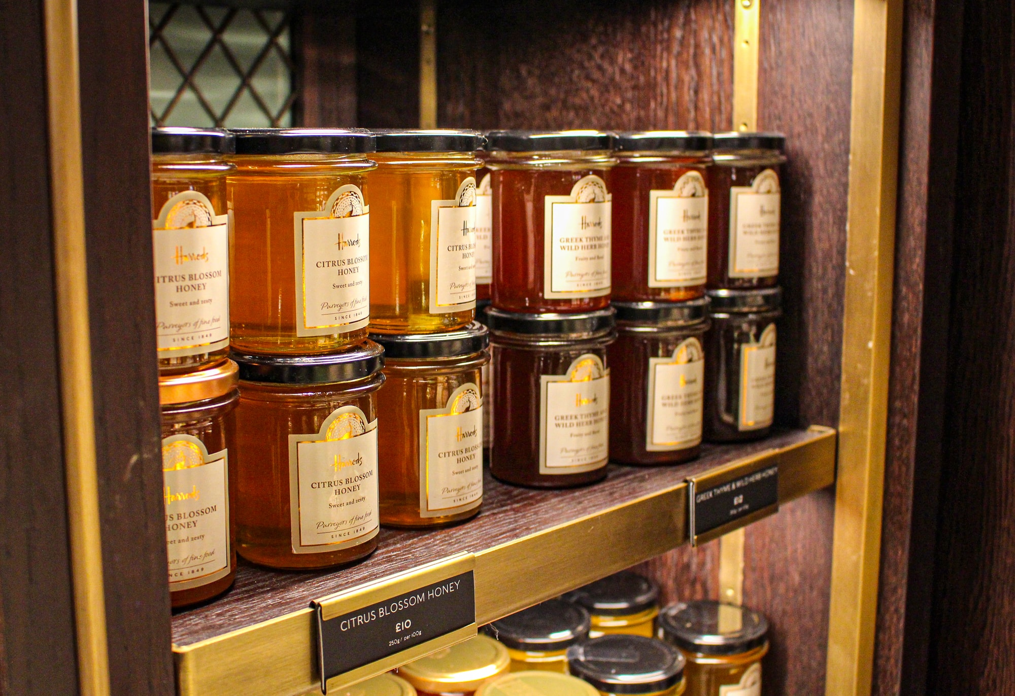 Honey, jams, preserves, marmalades in Harrods, Brompton Road, London, Great Britain: Citrus Blossom Honey, Greek Thyme Wild Herbs Honey, all in jars on wooden shelves.