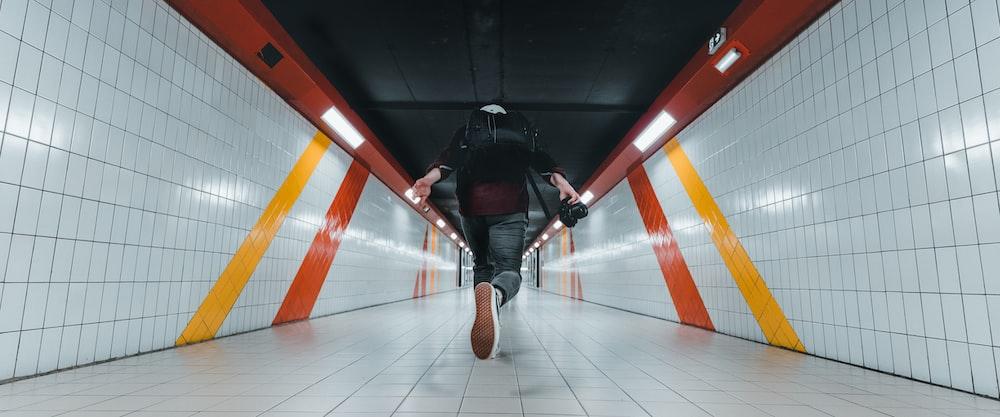 man in black jacket and black pants wearing black backpack walking on brown wooden floor