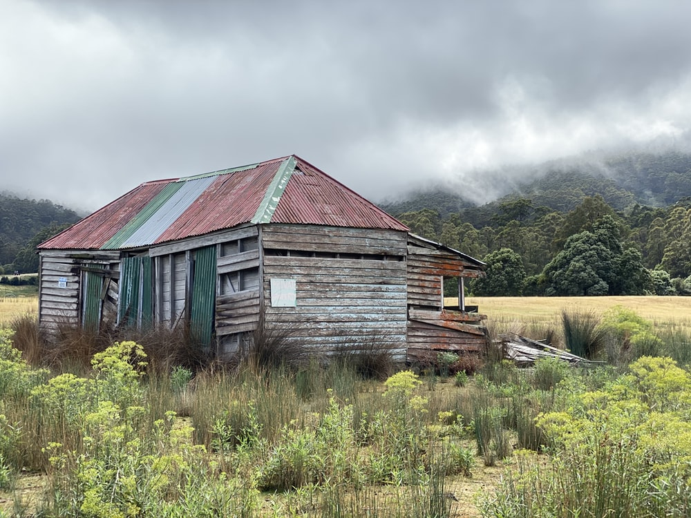 brown wooden house on green grass field under cloudy sky during daytime