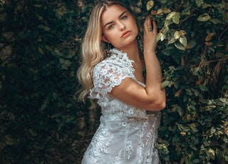 girl in white floral dress standing beside green plant