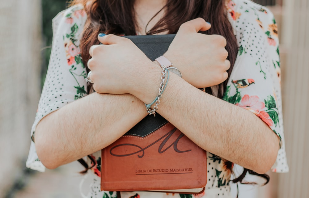 woman in silver bracelet holding brown book