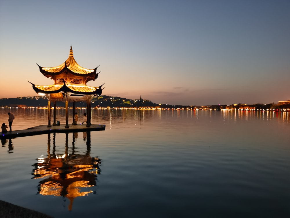 brown wooden gazebo on body of water during sunset