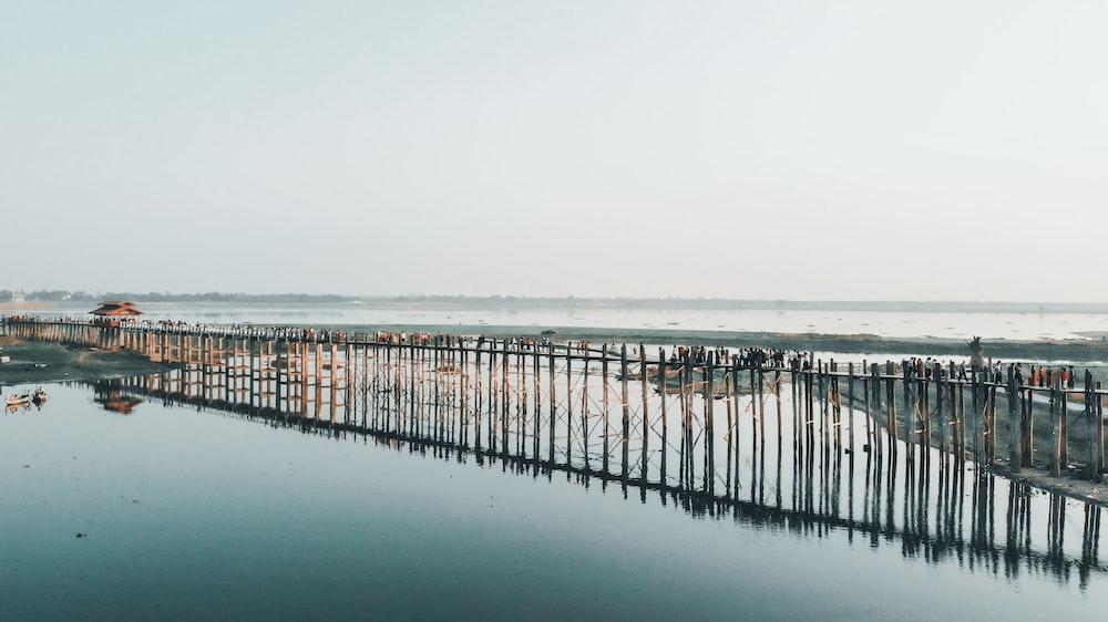 brown wooden dock on sea under white sky during daytime