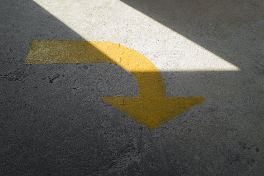 yellow arrow sign on gray asphalt road
