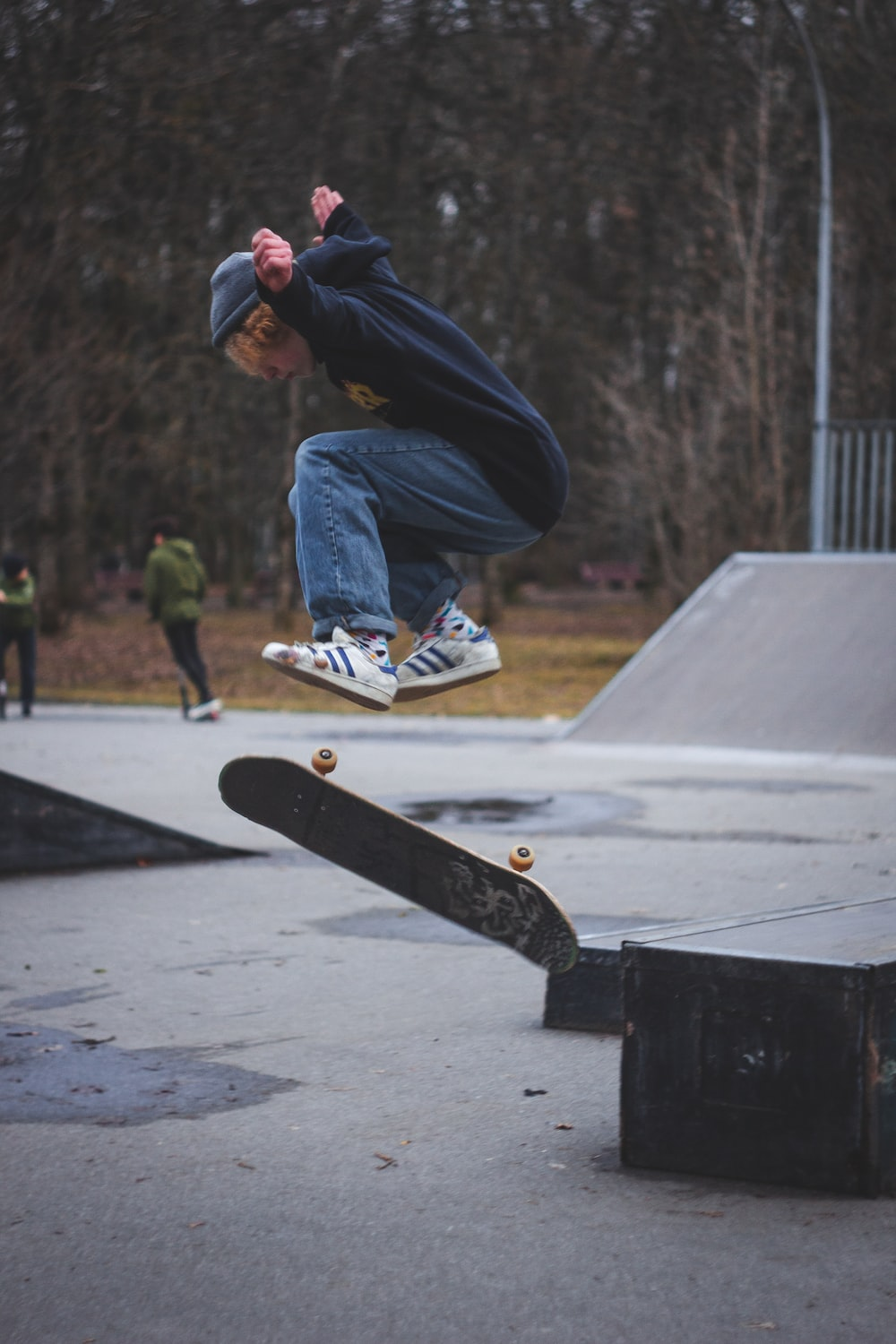 man in black hoodie and blue denim jeans riding skateboard during daytime