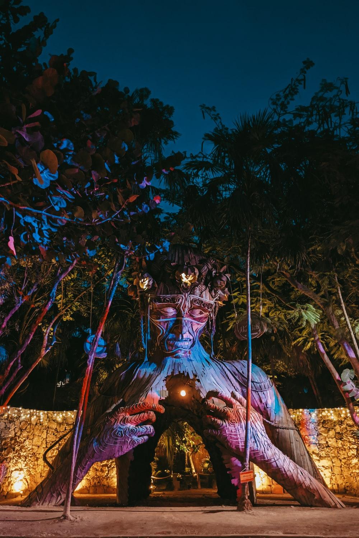 hindu deity statue near trees during night time