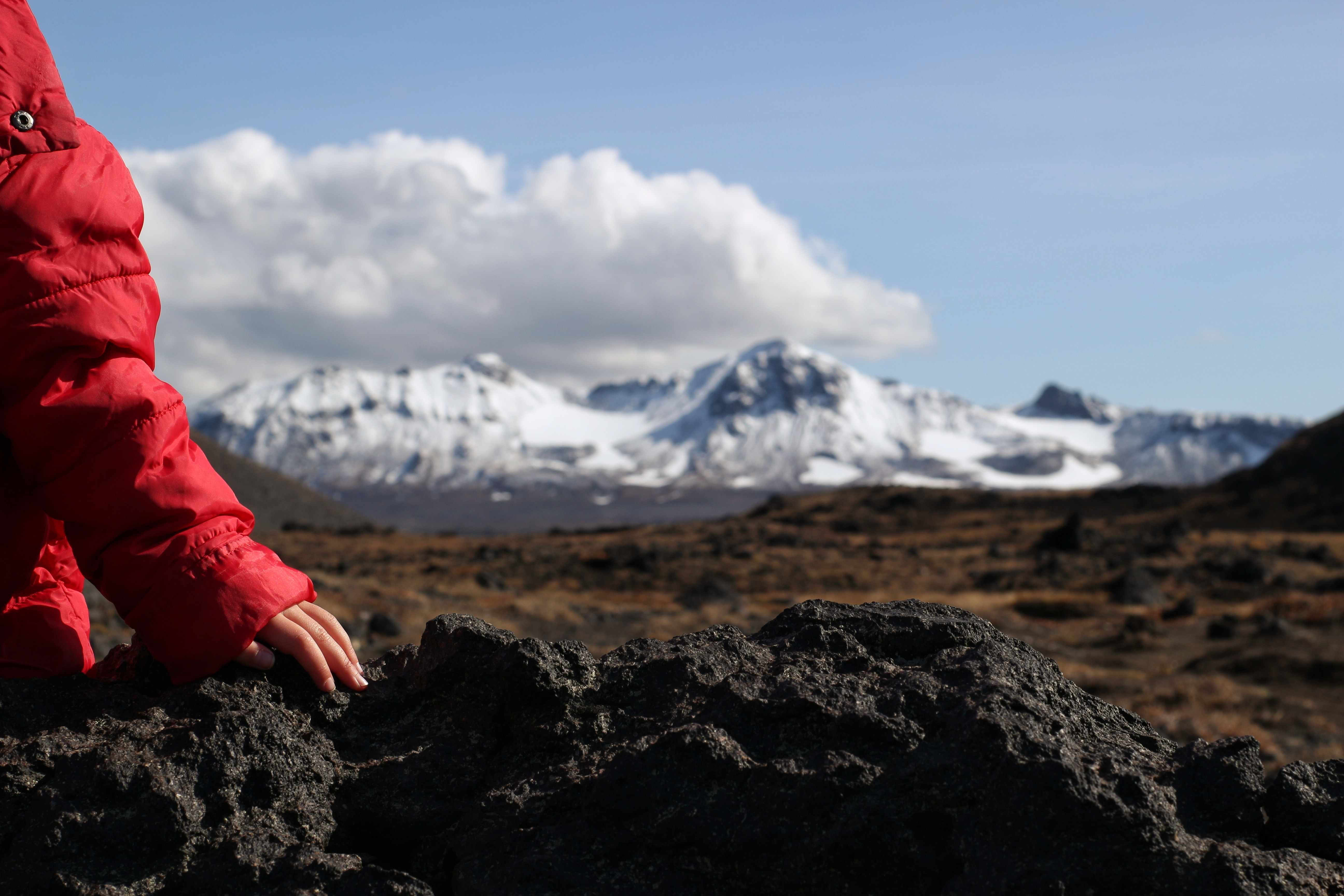 person in red jacket sitting on rock