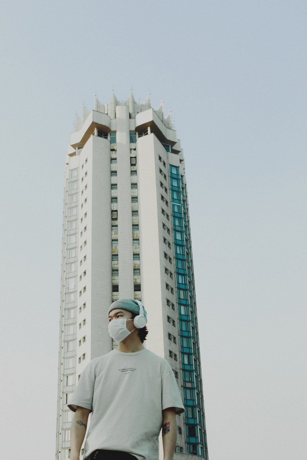 man in white shirt standing near high rise building during daytime