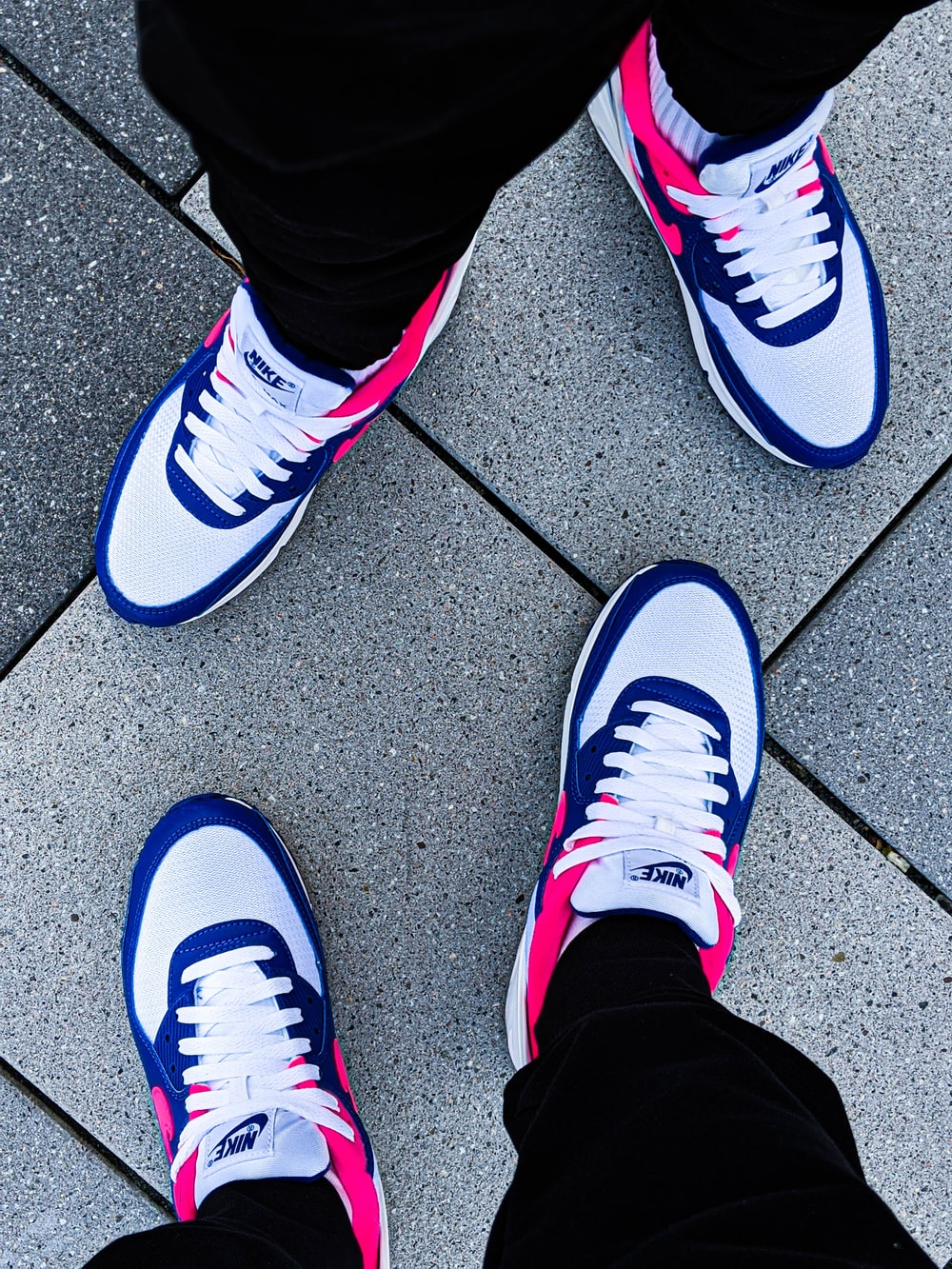 person wearing white and purple nike sneakers