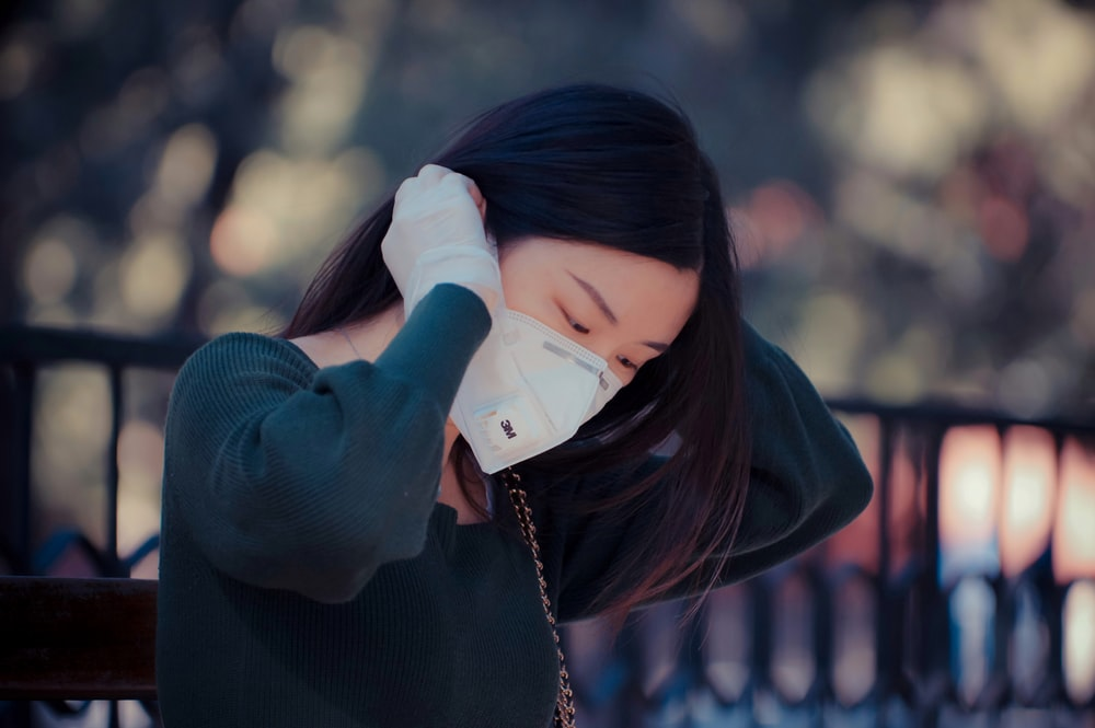 woman in black sweater covering her face with her hands