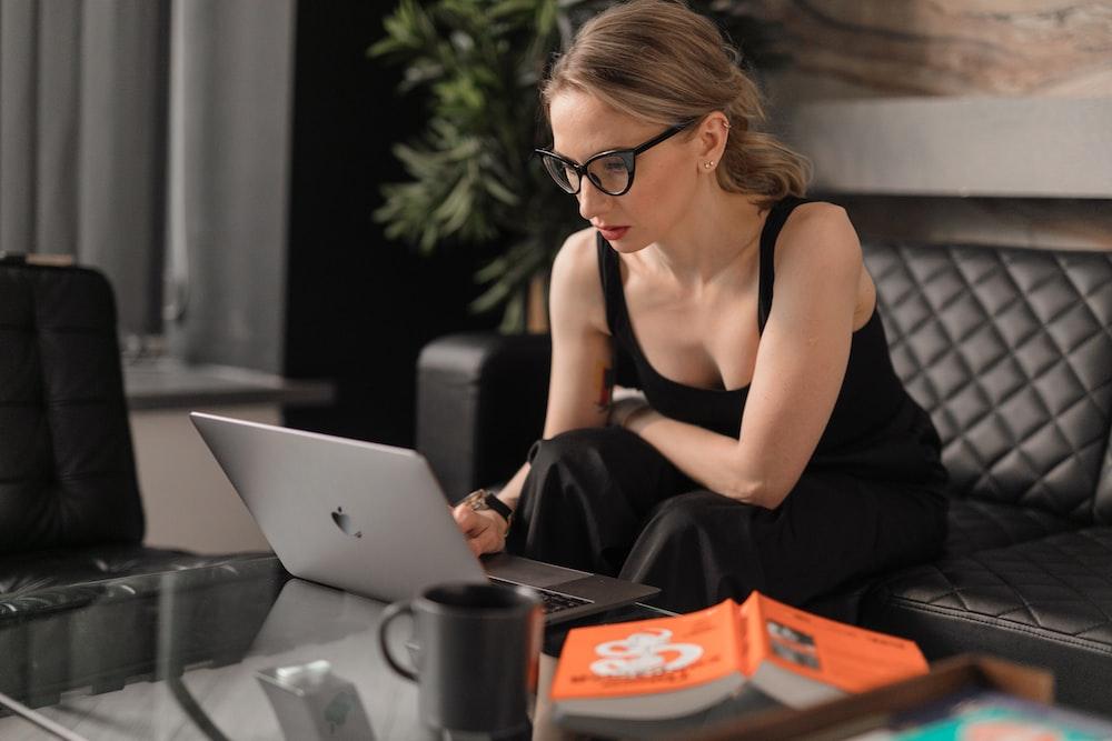 woman in black tank top using macbook
