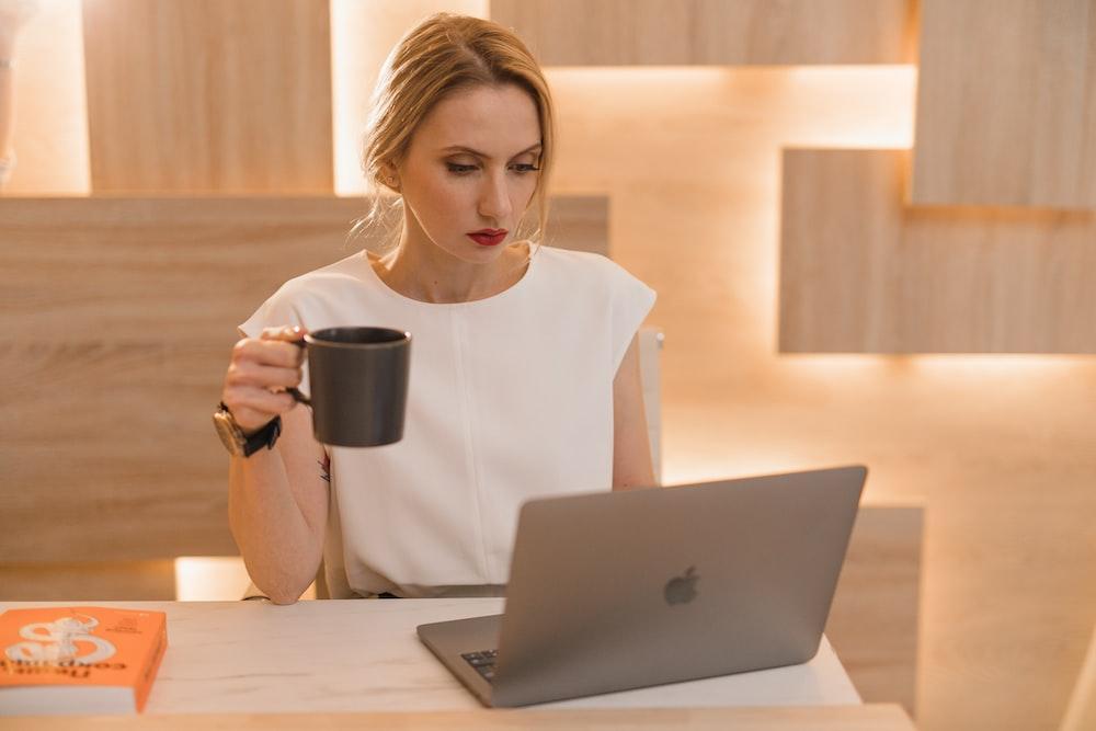woman in white crew neck t-shirt holding black ceramic mug