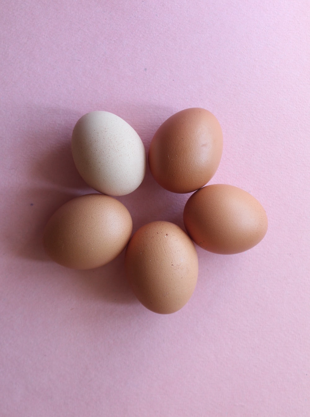 2 brown eggs on pink textile
