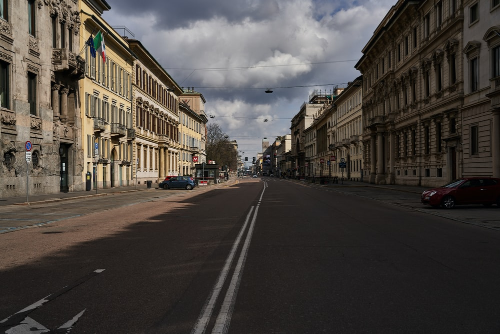 empty road between buildings under cloudy sky during daytime