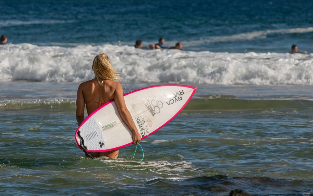 woman in pink bikini top holding white and red surfboard on beach during daytime