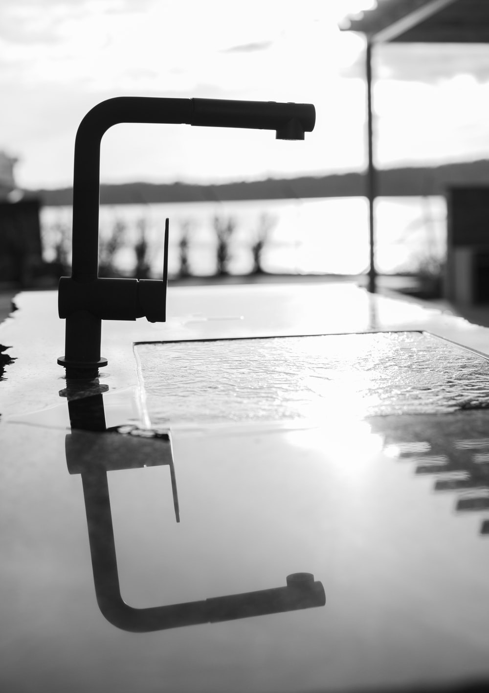 grayscale photo of water drop on wooden table