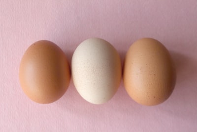 2 brown eggs on pink textile egg teams background