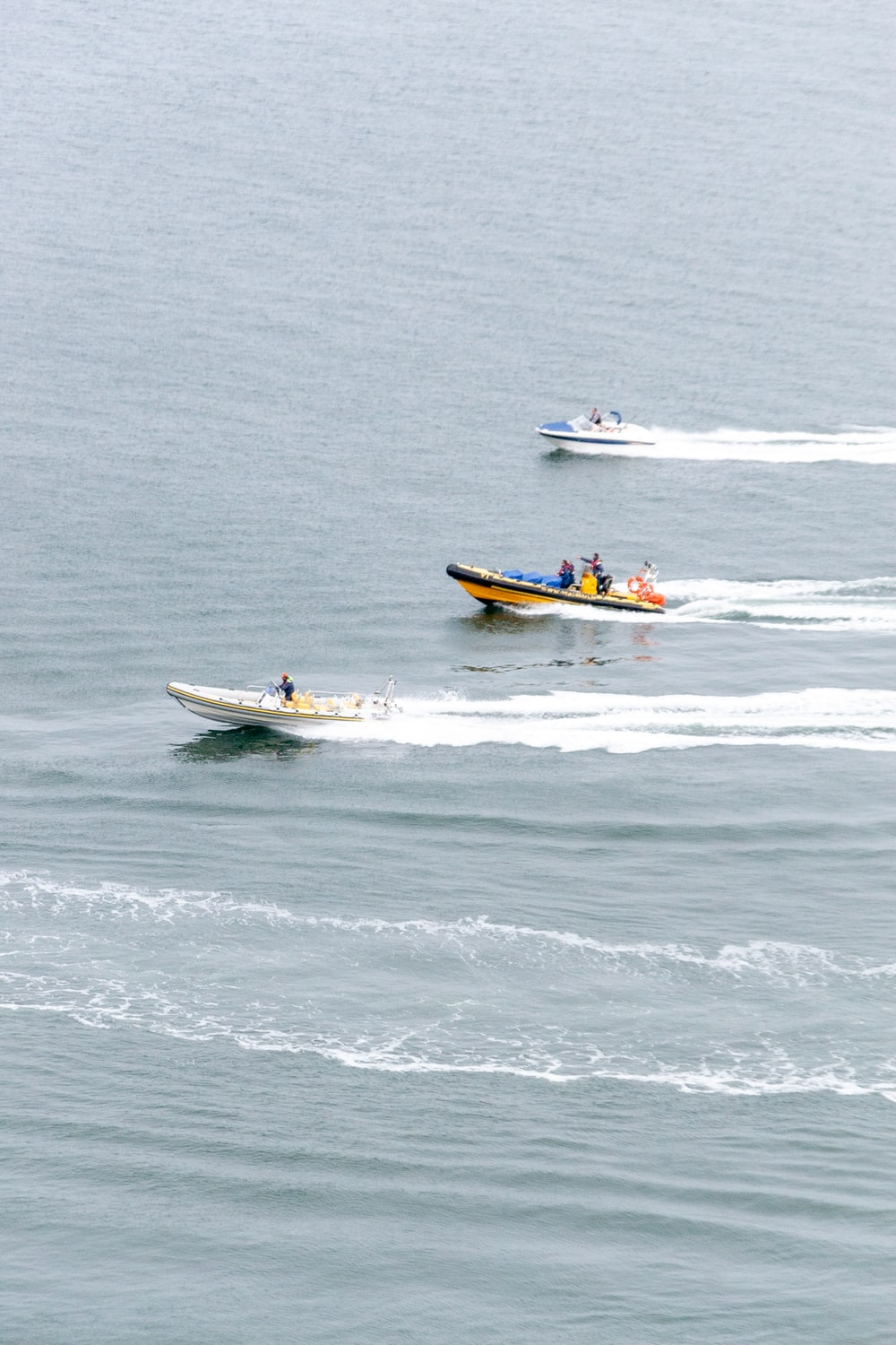 man in black shirt riding on white and yellow boat on sea during daytime