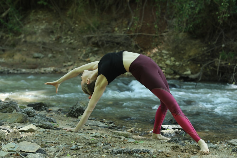 woman in black tank top and pink leggings doing yoga on brown sand during daytime