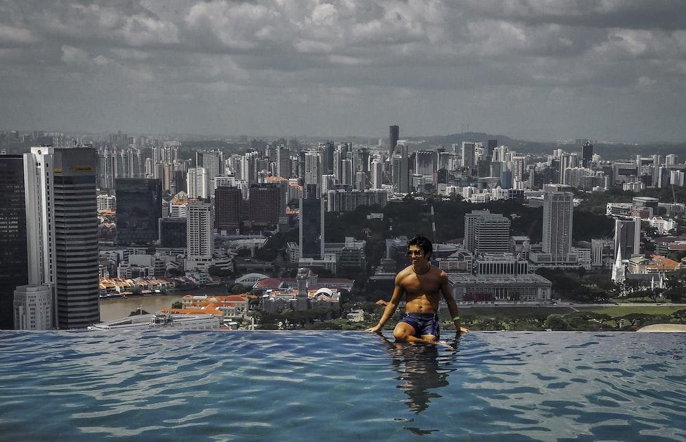 woman in black bikini top sitting on swimming pool during daytime
