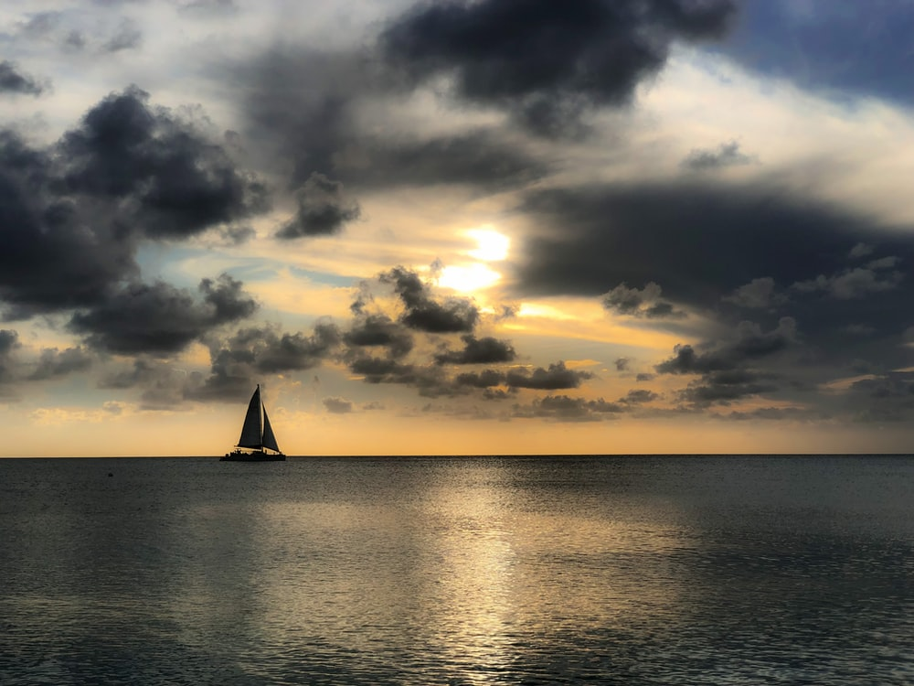 sailboat on sea under cloudy sky during daytime