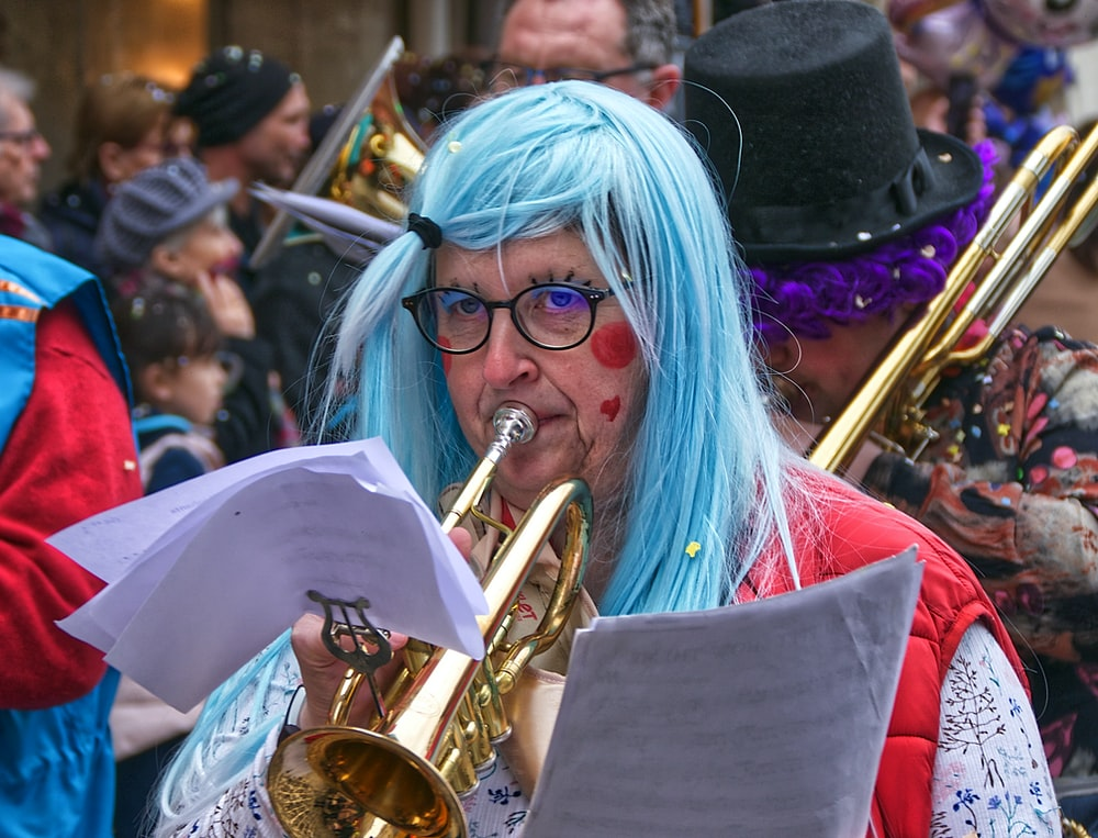 woman in white hair wearing red dress playing trumpet