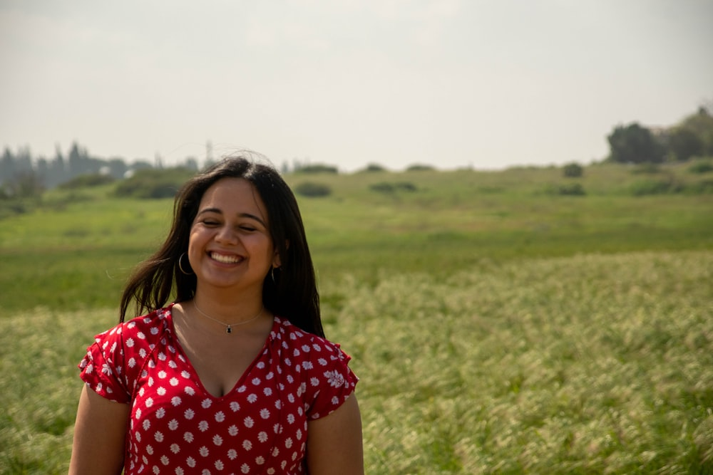 woman in red and white polka dot shirt standing on green grass field during daytime