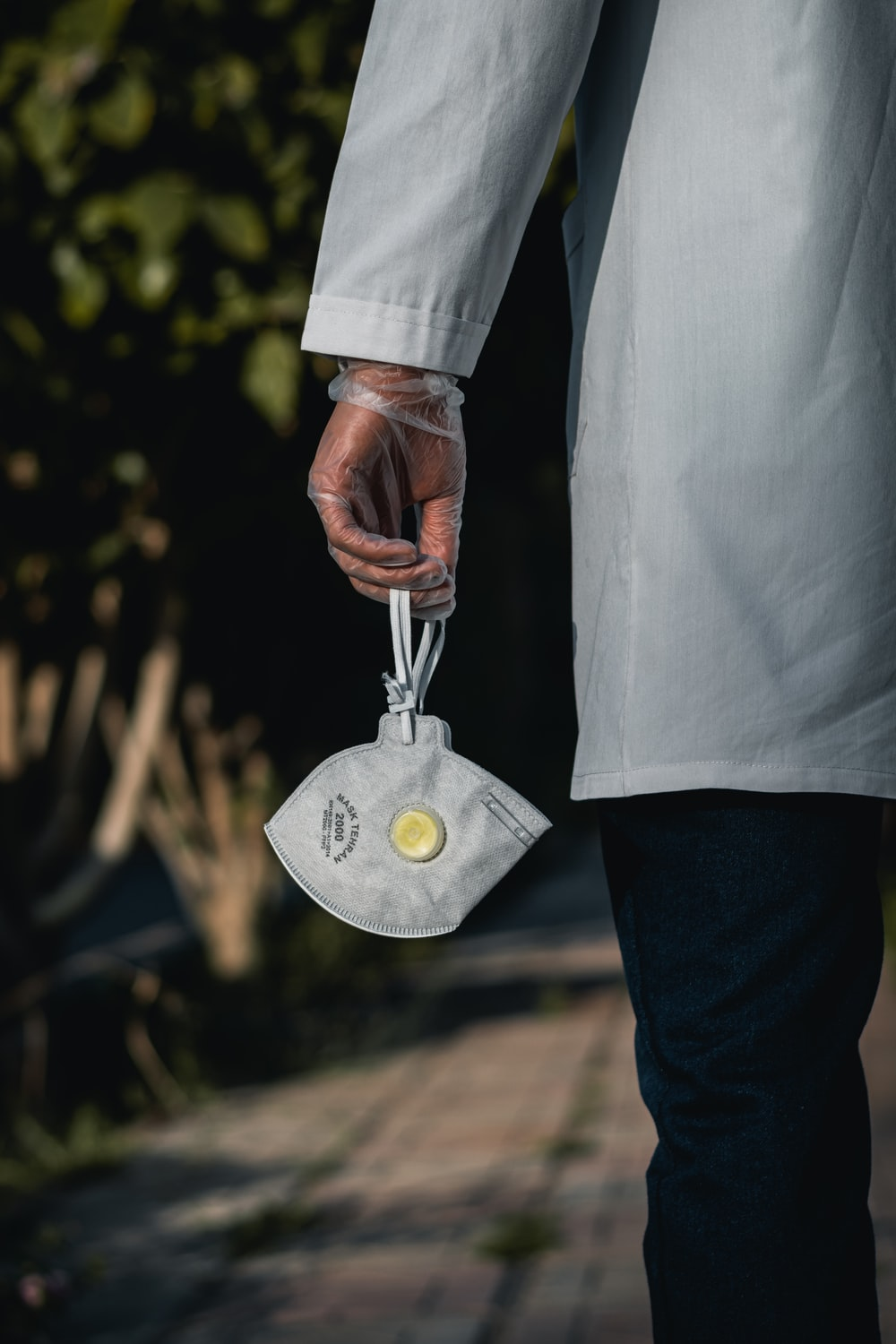 person in white dress shirt and blue denim jeans holding silver round pendant