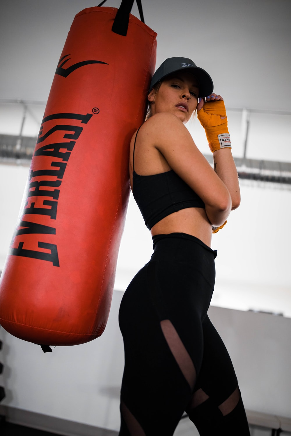 woman in black sports bra and black shorts leaning on orange and black boxing ring