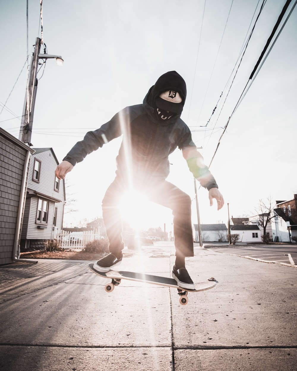 man in black hoodie and white pants riding skateboard during daytime