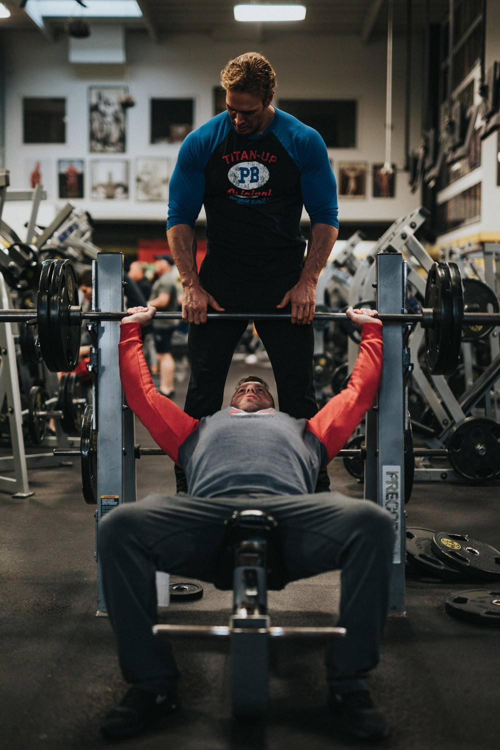 man in black crew neck t-shirt and gray pants sitting on black and red bench