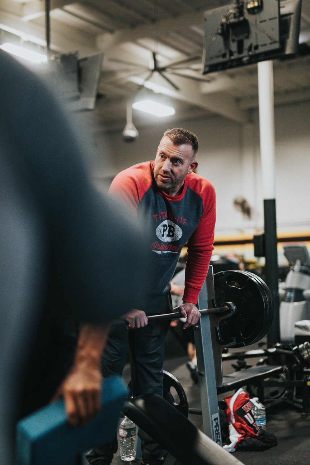 man in red and white crew neck long sleeve shirt holding black barbell