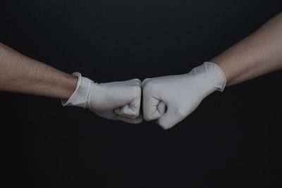 person wearing white long sleeve shirt and white gloves virus zoom background