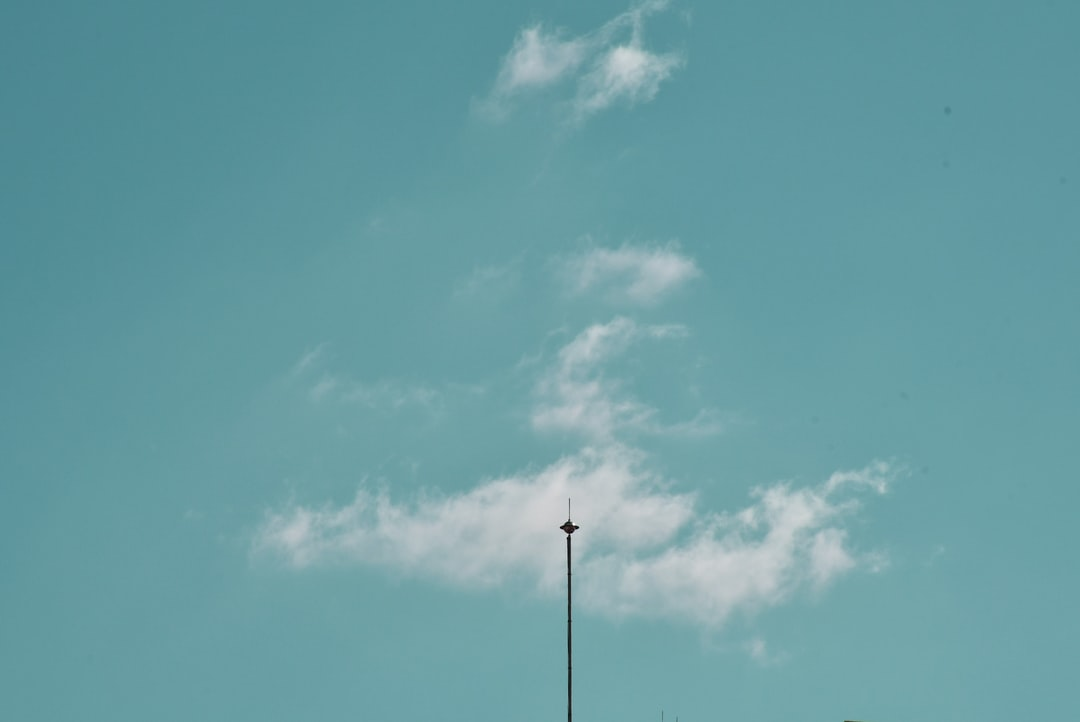 A minimal cloud and lightning rod in the sky.