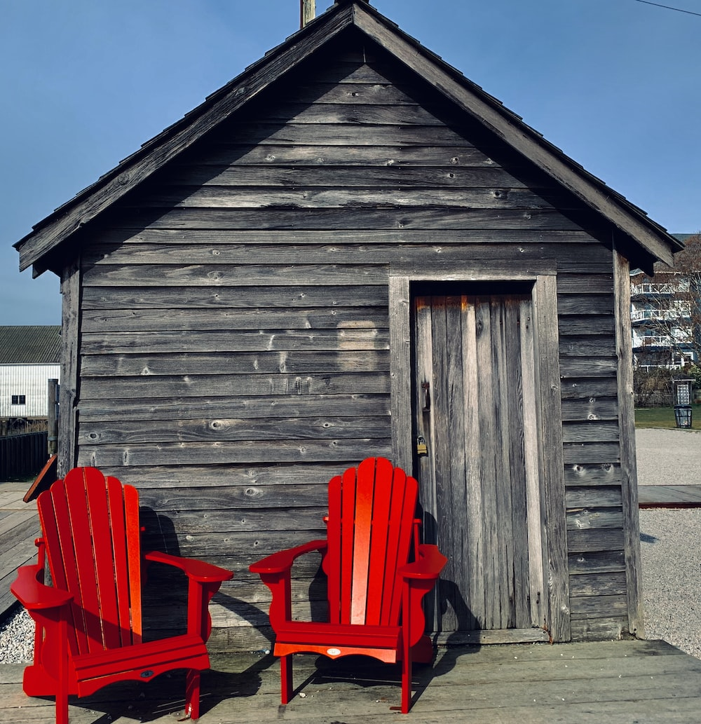 red wooden chairs near brown wooden house