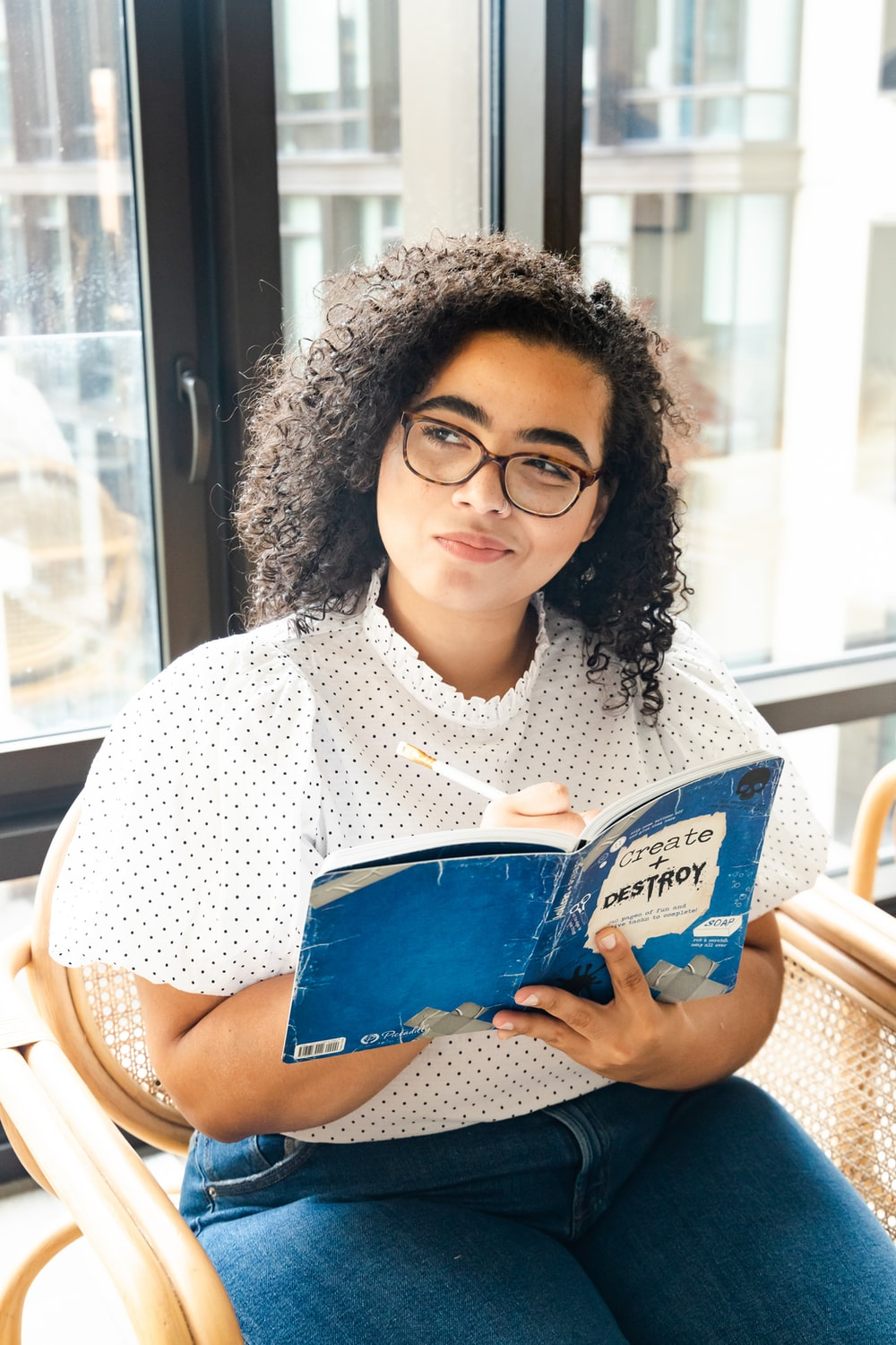 woman in white and black polka dot shirt holding blue and white book