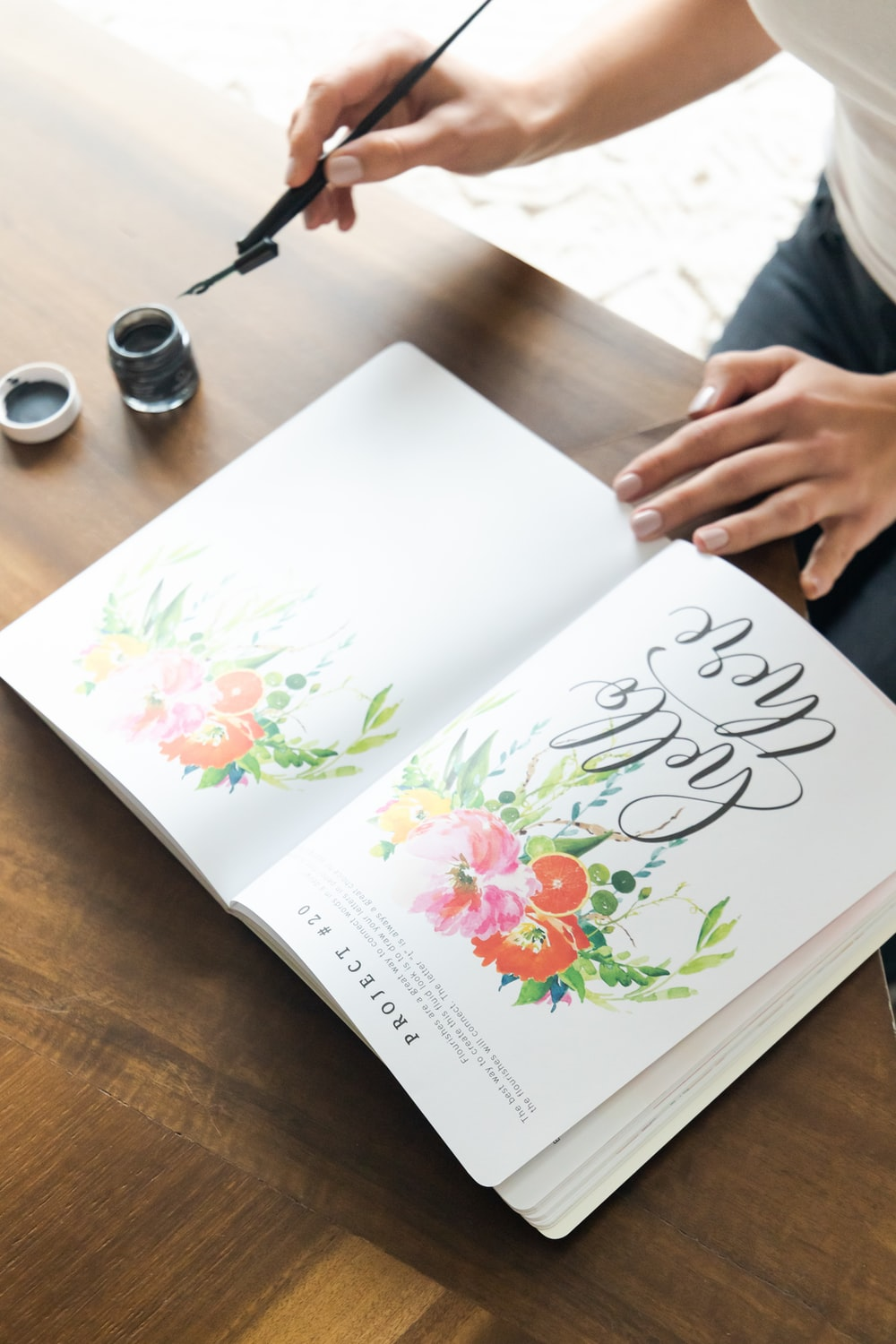person holding white and pink floral book