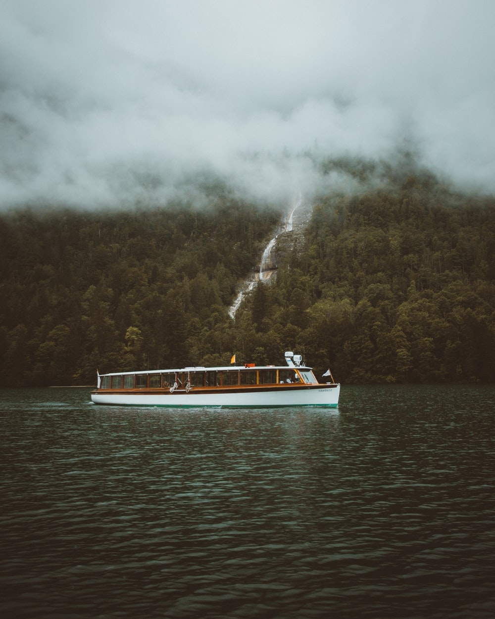 white and blue boat on water under white clouds