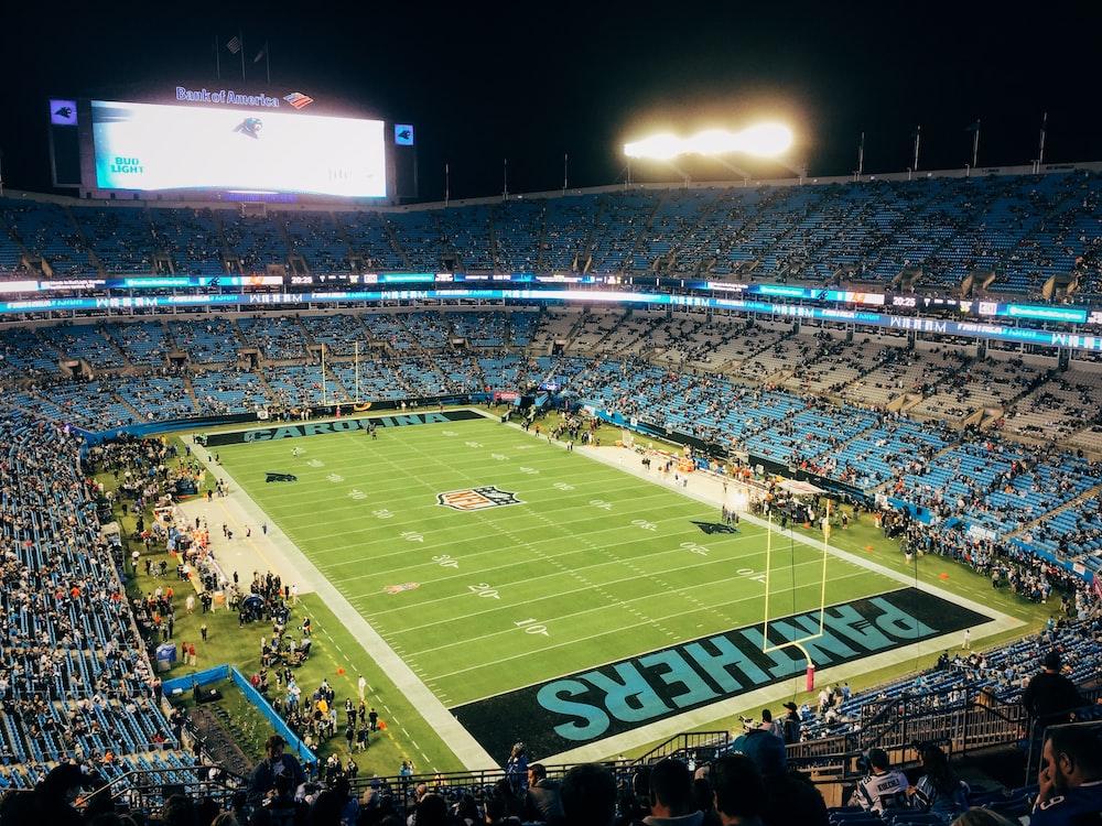 people watching football game during nighttime